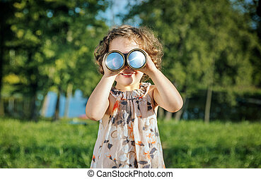 Portrait of a cheerful girl looking through the binoculars