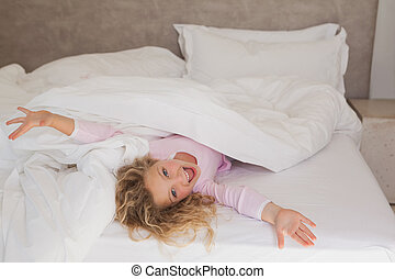 Portrait of a cheerful girl lying in bed