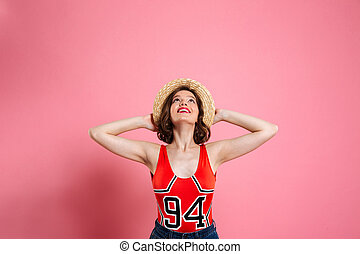 Portrait of a cheerful girl wearing swimsuit and straw hat...