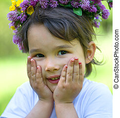 Portrait of a cheerful girl with a wreath of flowers on her head