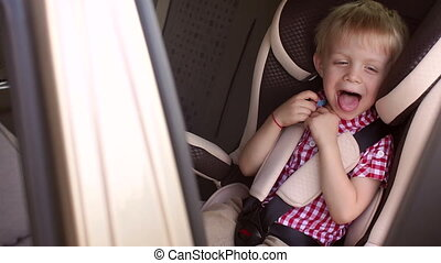 Portrait of a cheerful laughing boy in children's car seat during a summer trip.