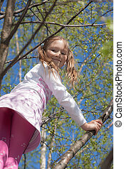 cheerful little girl on spring tree