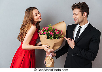 Portrait of a cheerful man giving his girlfriend flower bouquet