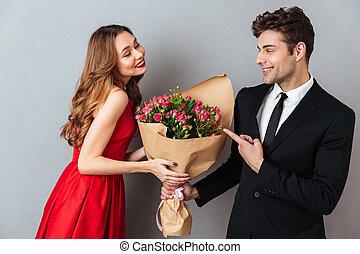 Portrait of a cheerful man giving his girlfriend flower bouquet