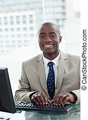 Portrait of a cheerful office worker using a computer in his...
