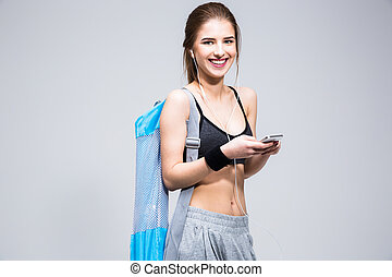 Portrait of a cheerful sports woman standing with smartphone