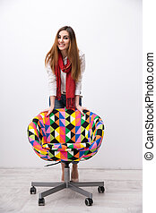 Portrait of a cheerful woman leaning on the colourful chair