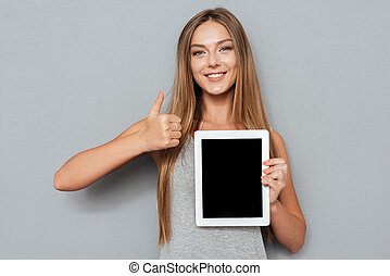 Portrait of a cheerful woman showing blank tablet computer screen