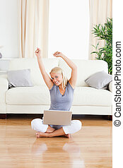 Portrait of a cheerful woman with a notebook while sitting on the floor in her lving room