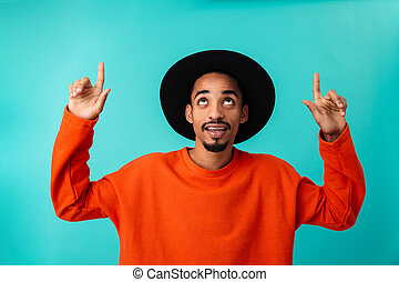 Portrait of a cheerful young afro american man in hat