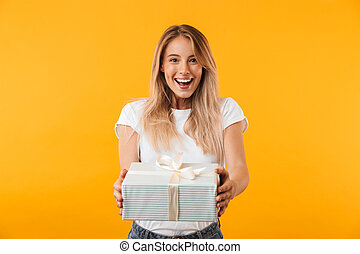 Portrait of a cheerful young blonde girl giving present box