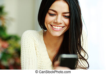 Portrait of a cheerful young woman using her smartphone