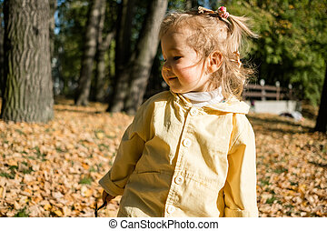 Portrait of a child girl walking in the park in autumn