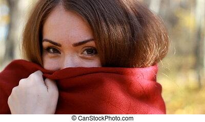 Portrait of a close-up woman who dresses a blanket. Cold weather on a sunny autumn day