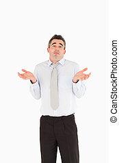 Portrait of a clueless businessman posing against a white ...