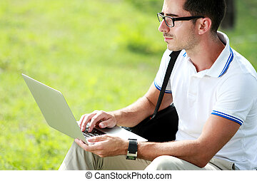 a college student sitting under the tree while studying using a