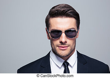 Portrait of a confident businessman in sunglasses looking at...
