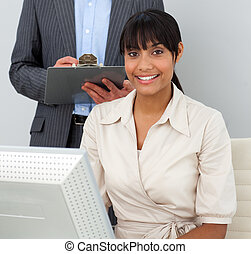Portrait of a confident businesswoman working at a computer