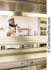 Portrait of a confident male chef in kitchen