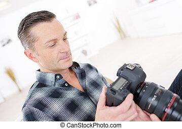 portrait of a confident photographer holding camera