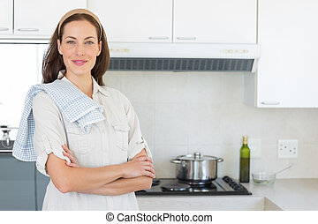 Portrait of a confident smiling woman in kitchen