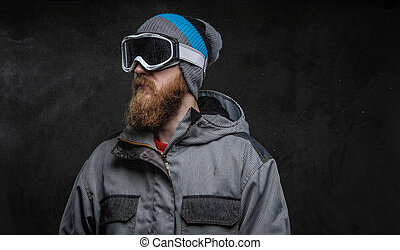 Portrait of a confident snowboarder wearing full protective equipment, isolated on a dark textured background.