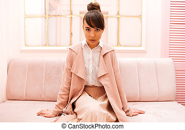 Portrait of a confident woman sitting on a sofa indoors