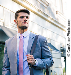 Portrait of a confident young businessman walking outdoors...