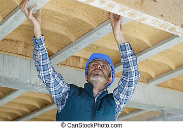 portrait of a construction worker on ceiling