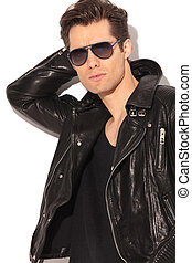 cool rocker in leather jacket holding hand behind head