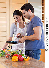 Portrait of a couple cooking with a pan