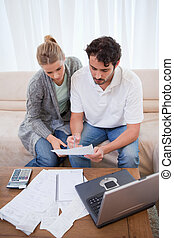 Portrait of a couple doing their accounting with a notebook