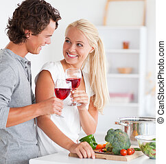 Portrait of a couple having a glass of red wine while...