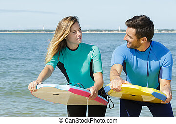 portrait of a couple holding bodyboards