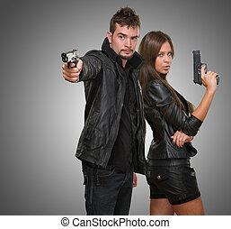 Portrait of a couple holding guns