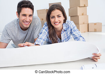 Portrait of a couple lying on the floor and holding a house plan in their new house
