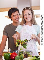 Portrait of a couple making a salad