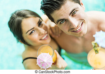 Portrait of a couple smiling and drinking a cocktail in a pool