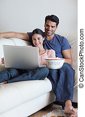 Portrait of a couple watching a movie while eating popcorn