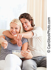 Portrait of a couple watching TV while eating popcorn