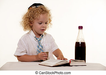 Portrait of a curly hair blond little three year old boy wearing white shirt and tie and a kippah jewish hat practicing the Sabbath ritual