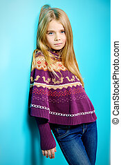 Portrait of a cute 7 year old girl wearing knitted clothes...