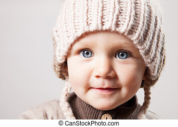 Portrait of a cute baby girl in a huge brown knitted hat. Isolated on white background.