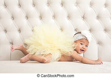 cute baby girl laying on a couch