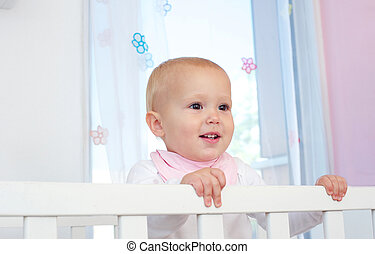 Portrait of a cute baby smiling in crib