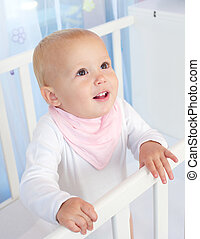 Portrait of a cute baby smiling in white crib