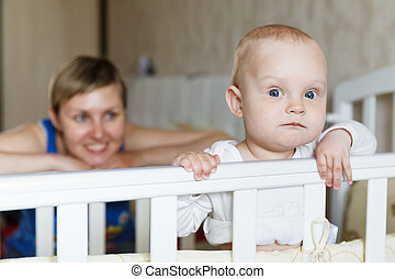 Portrait of a cute baby standing in bed