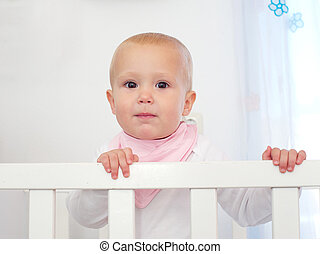 Portrait of a cute baby standing in white cot