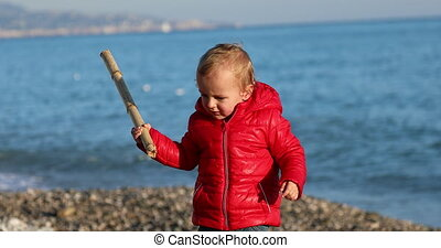 Boy Playing With A Bamboo Stick On The Beach