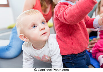 Portrait of a cute blond baby girl playing with colorful toys